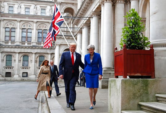 Britain's Prime Minister Theresa May, her husband Philip, President Donald Trump and first lady Melania Trump walk through the Quadrangle of the Foreign Office for a joint press conference in central London, Tuesday, June 4, 2019.