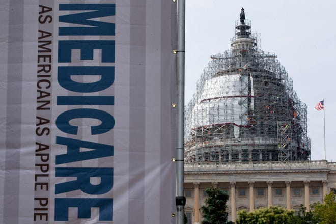 A sign supporting Medicare is seen on Capitol Hill in Washington in 2015. A report then said Medicare beneficiaries can end up with higher hospital bills for services as outpatients than inpatients.
