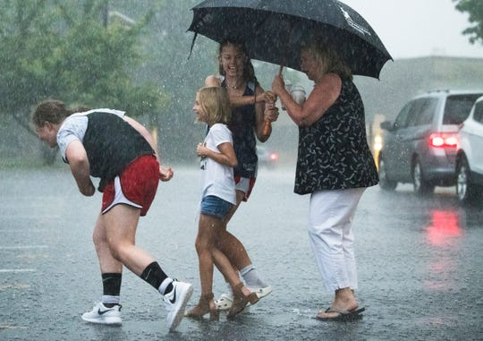 A family navigates through heavy rain as they head back to their car after attending Camden Catholic High School's promenade in Cherry Hill, NJ on Wednesday, May 29, 2019.