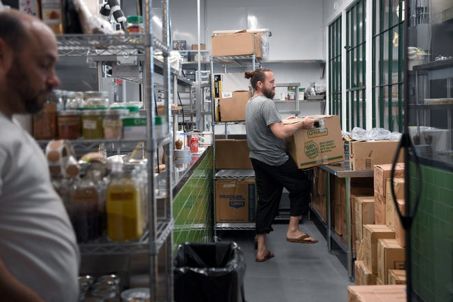 Chef Gavin Baker sorts through boxes of dishes so he can see one of each kind as he works in the kitchen of the soon-to-open restaurant by Noble Cider, The Greenhouse, on May 31, 2019.