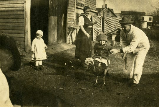In a photo taken before 1922, Mary and Stephen Mrlak play with their two daughters behind the Turf Exchange, now the CyberCafe West. A local landscaper Tuesday uncovered a hidden Prohibition Era cellar in the parking lot of the bar.