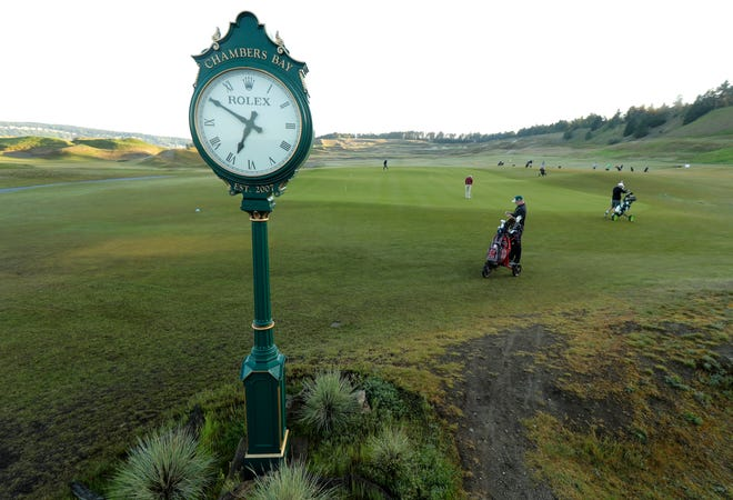 In this May 6, 2019, photo, early-morning golfers warm up in a practice area at Chambers Bay in University Place, Wash. Four years removed from the U.S. Open golf championship that was largely derided for its putting green problems, Chambers Bay may have salvaged its future in the championship rotation with a massive undertaking to replace every green on the course.
