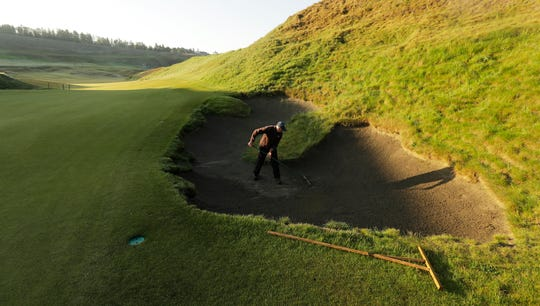 In this May 6, 2019, photo, Mark Braegelmann, a greenskeeper at Chambers Bay, works on a bunker at the 10th green at Chambers Bay in University Place, Wash. Four years removed from the U.S. Open golf championship that was largely derided for its putting green problems, Chambers Bay may have salvaged its future in the championship rotation with a massive undertaking to replace every green on the course.