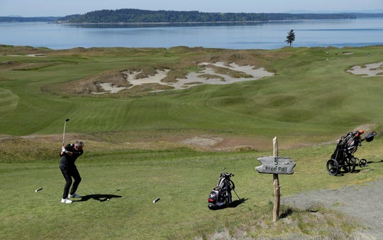 In this May 6, 2019, photo, PGA golf professional Jacob Lippold begins his swing on the fifth tee at Chambers Bay, in University Place, Wash. Four years removed from the U.S. Open golf championship that was largely derided for its putting green problems, Chambers Bay may have salvaged its future in the championship rotation with a massive undertaking to replace every green on the course.
