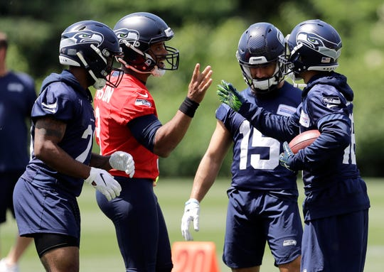 Seattle Seahawks quarterback Russell Wilson, second from left, greets Seattle Seahawks wide receiver Tyler Lockett, right, as wide receiver John Ursua (15) and running back J.D. McKissic, left, look on at the end of an organized team activity Tuesday, June 4, 2019, at the team's NFL football training facility in Renton.