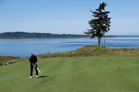 In this May 6, 2019, photo, PGA golf professional Jacob Lippold putts on the third green at Chambers Bay, in University Place, Wash. Four years removed from the U.S. Open golf championship that was largely derided for its putting green problems, Chambers Bay may have salvaged its future in the championship rotation with a massive undertaking to replace every green on the course.