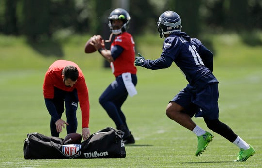 Seattle Seahawks quarterback Russell Wilson, center, passes to wide receiver Tyler Lockett (16) during an organized team activity Tuesday, June 4, 2019, at the team's NFL football training facility in Renton.