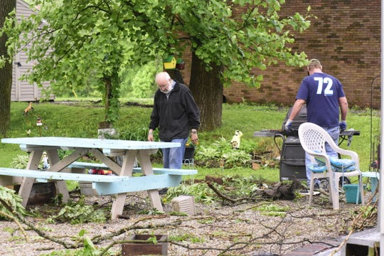 Dean Alexander gets some help from his son, Jeff Alexander, after a storm ripped down several limbs outside his Galion home Wednesday afternoon.