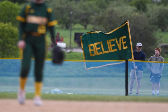 BFA fans hold up a flag in the outfield during the Division I softball semifinal game between the BFA St. Albans Comets and the Essex Hornets at Essex High School on Tuesday. afternoon June 4, 2019.