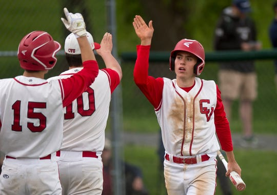 Champlain Valley's Jonah Roberts high-fives teammates after scoring against Rice during a Division I high school baseball semifinal game in Hinesburg on Tuesday, June 4, 2019.