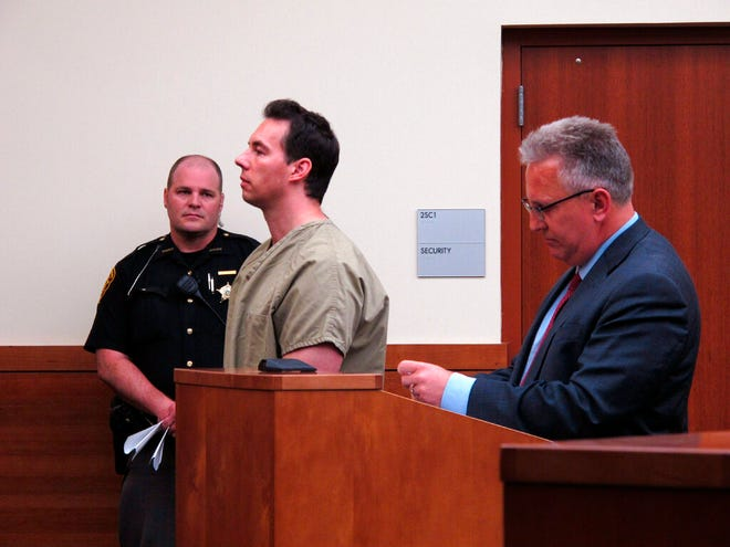Former critical care doctor William Husel, center, pleads not guilty to murder charges in the deaths of 25 hospital patients while appearing with defense attorney Richard Blake, right, in Franklin County Court on Wednesday, June 5, 2019, in Columbus, Ohio. Husel denies allegations that he ordered overdoses of painkillers for patients to hasten their deaths. (AP Photo/Kantele Franko)