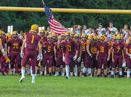 Ross players get ready to run onto their home field against the rival Harrison Wildcats, Sept. 14. The school is getting artificial turf