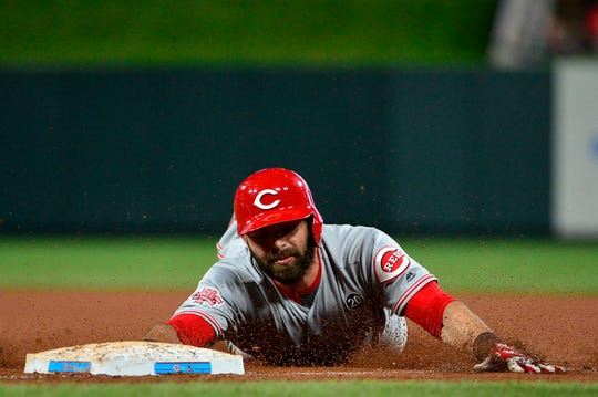 Jun 4, 2019; St. Louis, MO, USA; Cincinnati Reds left fielder Jose Peraza (9) slides back in at first after hitting a one run single off of St. Louis Cardinals starting pitcher Michael Wacha (not pictured) during the fifth inning at Busch Stadium. Mandatory Credit: Jeff Curry-USA TODAY Sports