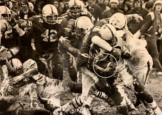 Western Hills quarterback Mike Isenogle is wrapped up by Elder tackle Tom Katenkamp (No. 77) after a short gain in the third period of the Turkey Day Classic Nov. 25, 1972. Also discernible in the mud  is No. 42, Elder's Jerry Vogele, and No. 81, Steve Grote.