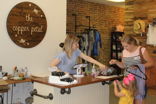 Megan Baggett, the owner of The Copper Petal, helps customers at her downtown Clarksville shop.
