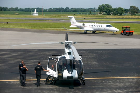 Operators mingle around a helicopter while a small jet is towed across the runway at the Clarksville Regional Airport in Clarksville, Tenn., on Tuesday, June 4, 2019.