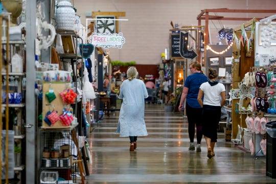 Operators of the small-business incubator walk down an aisle of booths at Miss Lucille's Marketplace in Clarksville, Tenn., on Tuesday, June 4, 2019.