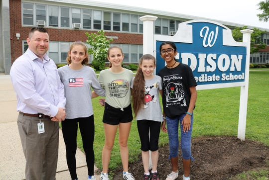 (From left) Edison Intermediate School Principal Dr. Matthew Bolton congratulates 8th grader Gabriela Gil and 7th graders Sofia Gil, Hannah Hollosi and Anusha Iyer, who are finalists in a national STEM competition.
