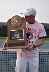 Ames coach Dustin Rhoads kisses the state championship trophy after the Little Cyclones won the 2A team tennis title.