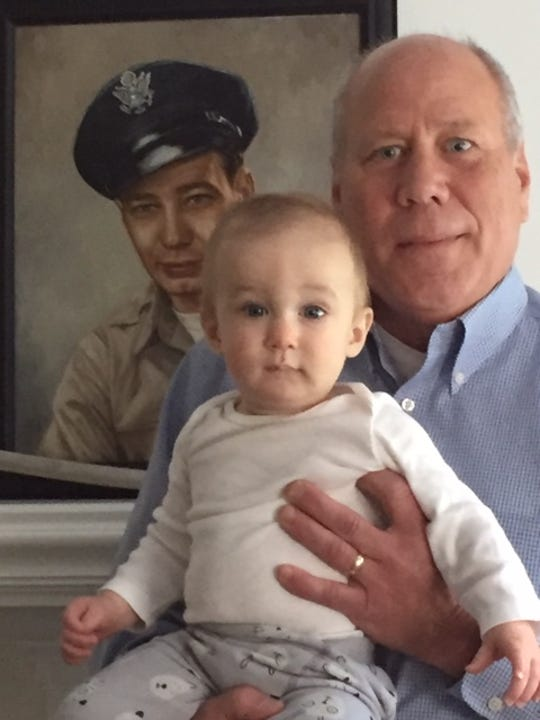Grandfather Mike Rowley of Clive with his grandson, Isaac, in front of a portrait of great-grandfather Denton Rowley.