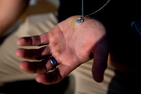 Peyton Paddock, redshirt senior kicker for the Iowa State football team, holds the pendent, his brother's finger print, on the necklace he's wearing while sitting in the stands of Jack Trice Stadium on Wednesday, June 5, 2019, in Ames. Paddock's brother was killed by a drunk driver in 2016.
