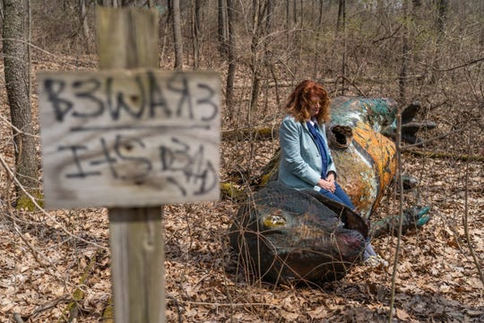 Sandra Crabb, 77, sits on a dinosaur that was vandalized at the Prehistoric Forest in Irish Hills.
