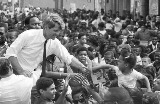 Robert F. Kennedy  reaches out to touch 4 year-old Sybil (Turnner) Martin, as he campaigned at 12th Street and Clairmont in Detroit, May 1968.