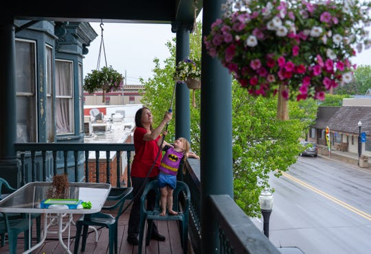 Yale Hotel manager Shelley O'Brien is helped by Aster Murray while watering hanging baskets from a balcony of the hotel in Yale, Michigan, on Thursday, May 30, 2019. O'Brien has invited women in states that have recently restricted access to abortion to come to Michigan. O'Brien offered in a Facebook post to put the women up for free at the hotel, and provide them transportation to their medical appointments.