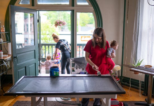 Yale Hotel manager Shelley O'Brien holds her granddaughter Amia O'Brien while painting a section of a door at the hotel in Yale, Michigan, on Thursday, May 30, 2019. O'Brien has invited women in states that have recently restricted access to abortion to come to Michigan. O'Brien offered in a Facebook post to put the women up for free at the hotel, and provide them transportation to their medical appointments here.