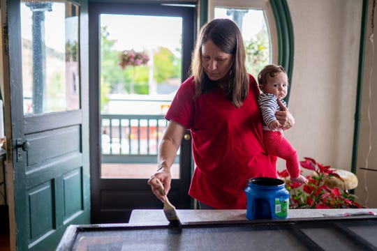 Yale Hotel manager Shelley O'Brien holds her granddaughter Amia O'Brien while painting a door at the hotel in Yale, Michigan, on Thursday, May 30, 2019. O'Brien has invited women in states that have recently banned or restricted abortions to come for access to reproductive health services. O'Brien offered in a Facebook post to put the women up for free at the hotel, and provide them transportation to their medical appointments here in Michigan.