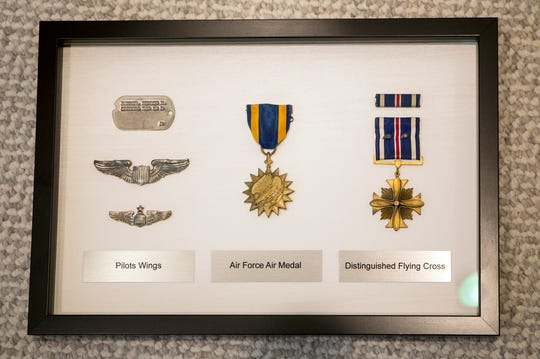 A dog tag, pilots wings, an Air Force Air Medal and Distinguished Flying Cross belonging to Mort Harris for his WWII service is framed and hanging in his home in Bloomfield Hills on Monday, June 3, 2019.