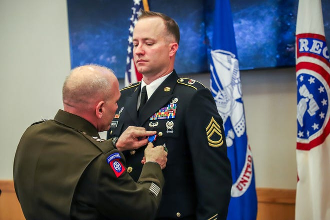 Sergeant First Class Gregory Waters receives the Distinguished Service Cross award from U.S. Army Recruiting Command Major General Frank Muth, during a ceremony at Selfridge Air National Guard Base in Harrison Twp., Mich. on Wednesday, June 5, 2019. Waters is receiving the medal for heroism as a medic in Afghanistan in 2008.