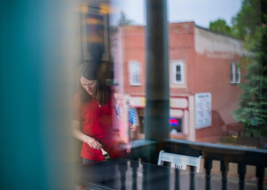 Yale Hotel manager Shelley O'Brien is seen through a wavy glass window while holding her granddaughter Amia O'Brien. She is painting a door at the hotel in Yale, Michigan, on Thursday, May 30, 2019. O'Brien has invited women in states that have recently restricted access to abortion to come to Michigan. O'Brien offered in a Facebook post to put the women up for free at the hotel, and provide them transportation to their medical appointments.