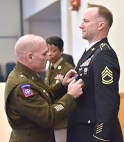 Maj. Gen. Frank Muth, left, commanding general for the U.S. Army Recruiting Command, pins the Distinguished Service Cross onto the jacket of Sgt. 1st Class Gregory A. Waters, right, during a ceremony at Selfridge Air National Guard Base on Wednesday.