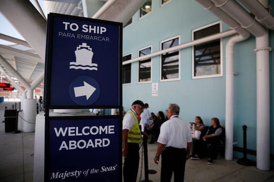 People stand near a sign directing passengers to a cruise ship at Port Everglades on Wednesday, June 5, 2019, in Fort Lauderdale, Fla.