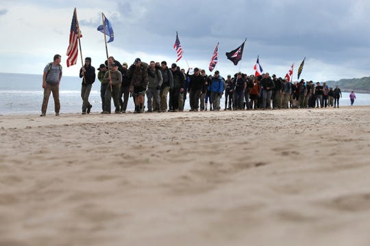 WWII enthusiasts walk on Omaha beach, Normandy, Wednesday June 5, 2019. Extensive commemorations are being held in the U.K. and France to honor the nearly 160,000 troops from Britain, the United States, Canada and other nations who landed in Normandy on June 6, 1944 in history's biggest amphibious invasion.