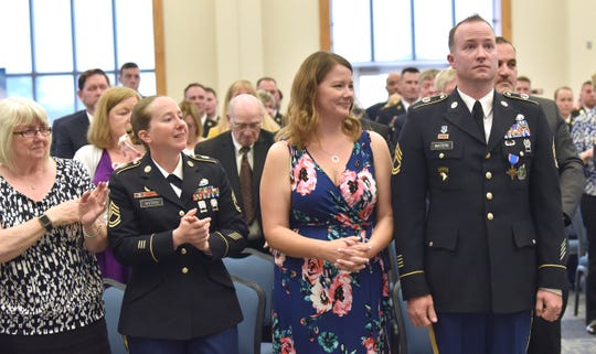 Sgt. 1st Class Gregory Waters' mother, Debbie Waters, from left, his sister, U.S. Army Sgt. 1st Class Bethany Waters, and his wife, Jill Waters, clap as Waters from the Eastpointe Army Recruiting Station stands at attention at the end of the ceremony.