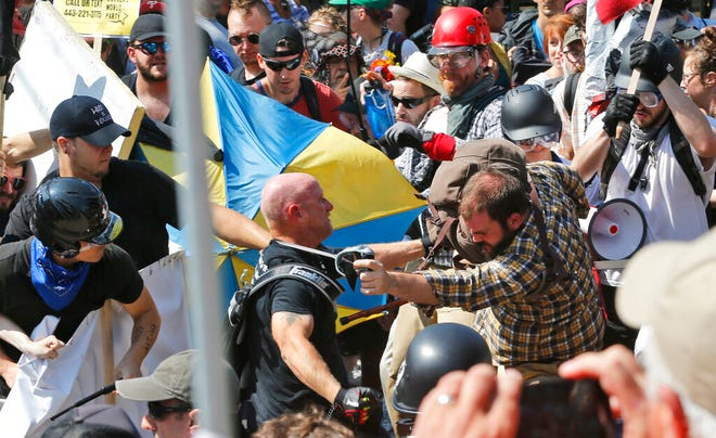 In this Aug. 12, 2017 file photo, white nationalist demonstrators clash with counter demonstrators at the entrance to Lee Park in Charlottesville, Va. Federal charges against three alleged members of a violent white supremacist group accused of inciting violence at California political rallies were dismissed Monday, June 3, 2019, by Judge Cormac J. Carney in U.S. District Court in Los Angeles, who found their actions amounted to constitutionally protected free speech.