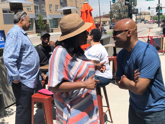 In this June 1, 2019, photo, Denver Mayor Michael Hancock, right, chats with a voter during a rally for Hancock's re-election bid in Denver. Former Denver Mayor Wellington Webb is chatting with a voter in back. Hancock, who is seeking his third term, is facing a runoff election Tuesday against Jamie Giellis. (AP Photo/James Anderson)