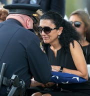 Nadereh Johnson receives the flag from her husbandÕs casket at his funeral on Wednesday, June 5, 2019.