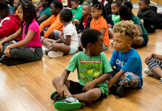 Caidence Campbell, left front, checks on Jarrell Stafford during meditation at the Quality Life Center after-school program in Fort Myers.