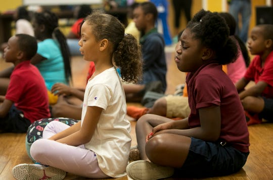 Ca'mari Bryant and Jamyrah Wardlow meditate with other students at the Quality Life Center after-school program on Tuesday, May 21, 2019, in Fort Myers.