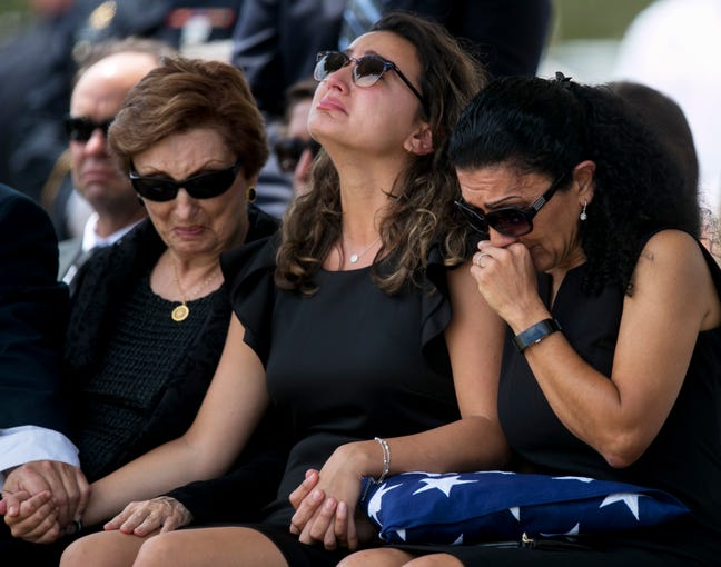 Captain Jospeh Johnson's daughter Ariana, center, and his wife Nadereh grieve at his funeral on Wednesday, June 5, 2019, in Estero. Capt. Johnson, who worked for the Seminole Police Department, passed away in the line of duty on May 30, 2019.
