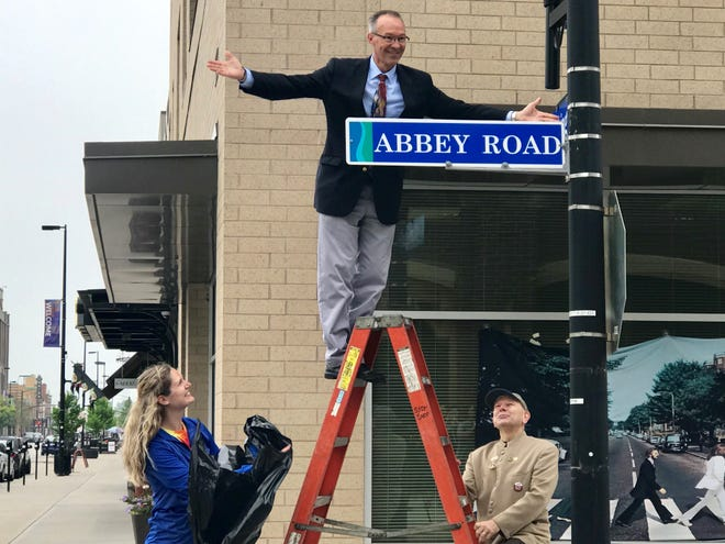 Jeff Mirkes, executive director of Downtown Green Bay Inc., unveils the street sign that reflects CityDeck Court's new name as Abbey Road in honor of Paul McCartney's concert Saturday at Lambeau Field. The sign, revealed Wednesday, will stay up through the weekend.