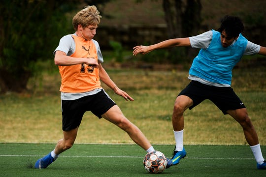 Conor Dowler, a junior at TL Hanna, left, attempts to gain possession of the ball during Greenville FC practice at the Kroc Center Wednesday, June 5, 2019.