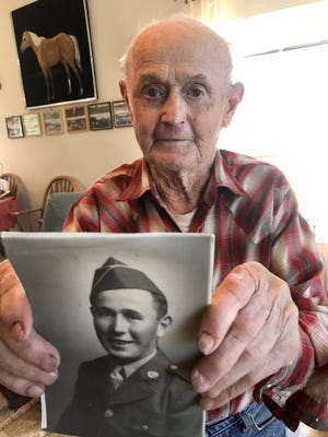 Tim McAllister holds a 75-year-old photo of himself in his Army uniform. The Geyser man served in the Philippians during World War II, with brothers fighting in the Aleutians and Europe. Two brothers crossed the English Channel with the D-Day invasion.