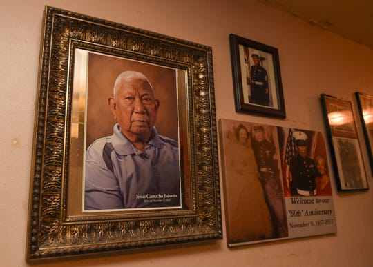 Photos of World War II survivors and married couple, Jesus and Floripies Babauta and their family through the years, are displayed at their home in Santa Rita on June 5, 2019.