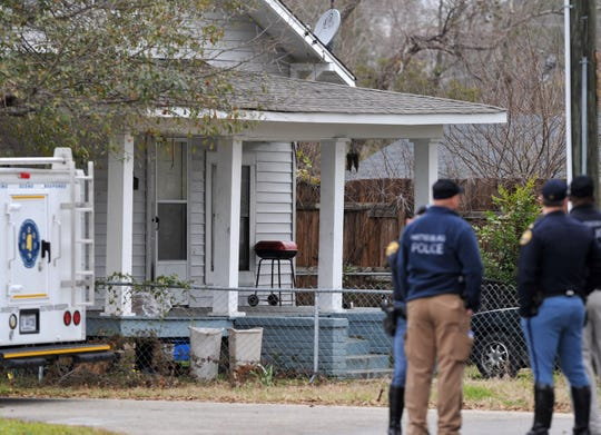 Hattiesburg police gather in front of a house on the 800 block of Dabbs Street where two women and a fetus were killed on Monday, Feb. 22, 2010.