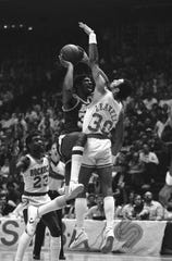Earvin Magic Johnson (32) of the Los Angeles Lakers drives the lane over Houston Rockets Allen Leavell (30) late in the game, Friday, April 14, 1981, Houston.