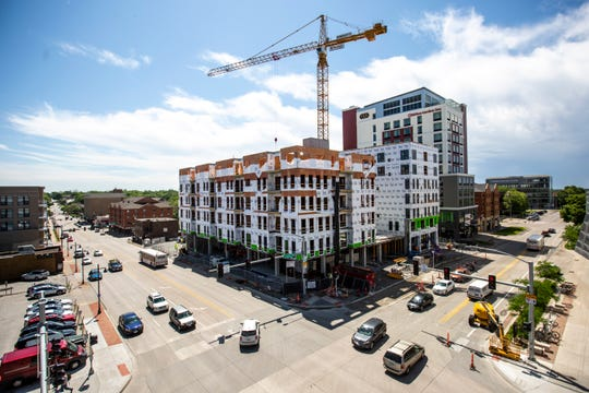 Cars and buses drive along Burlington and Clinton Streets as construction continues, Wednesday, June 5, 2019, at Hieronymus Square in downtown Iowa City. Iowa City Council approved an $8 million tax increment financing package to develop a lot that was previously sat vacant.